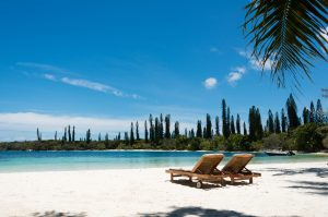 Kanumera beach on the Isle of Pines in New Caledonia. There are a pair of beachchairs on the white sand. The bay is surrounded by pacific cedars and is known as one of the most beautiful bays in the world.